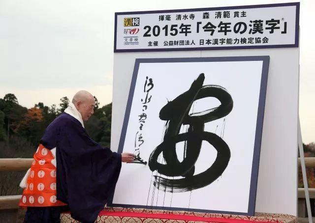 """2015年12月15日,在日本京都,清水寺住持森清范写下日本2015年度字""""安""""字。(新华社/法新)"""